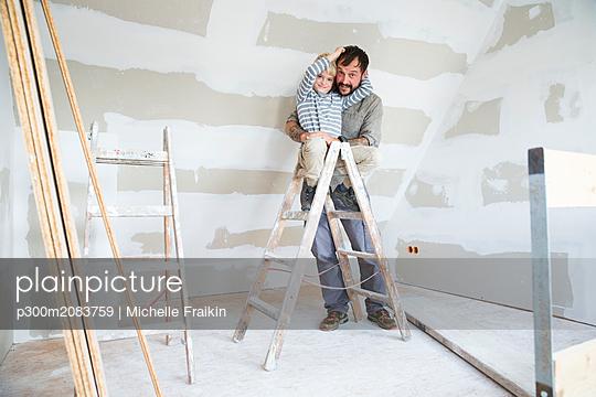 Portrait of happy father and son working on loft conversion - p300m2083759 von Michelle Fraikin
