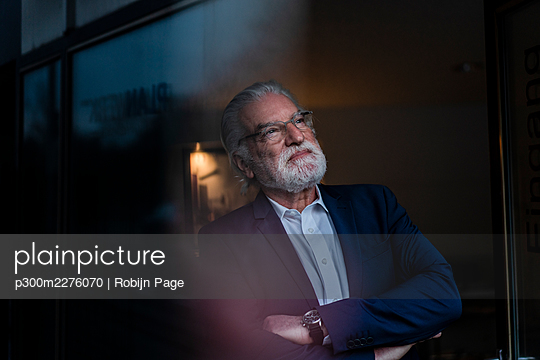 Smiling businessman with arms crossed at office during night - p300m2276070 by Robijn Page