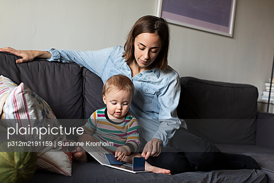 Mother reading book to baby - p312m2191159 by Susanne Kronholm