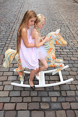 Two girls on a rocking horse - p045m853388 by Jasmin Sander