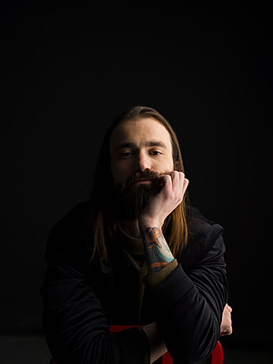 Portrait confident tattooed brunette man with beard against black background - p1192m1403625 by Hero Images