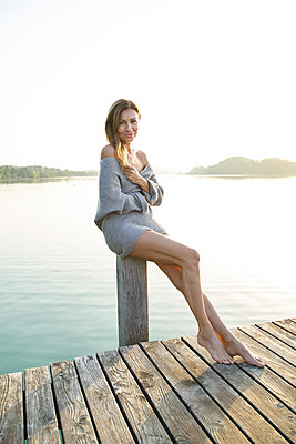 Portrait of mature woman on jetty sitting on pole at a lake - p300m2140676 by Philipp Nemenz