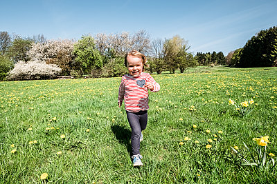 Portrait of happy little girl running on a meadow - p300m2167002 by Wilfried Feder