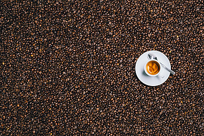 Directly above shot of espresso cup on roasted coffee beans - p301m1498790 by Norman Posselt