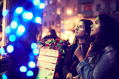 Lesbian couple looking at menu while standing against concession stand at night - p426m2165546 by Maskot
