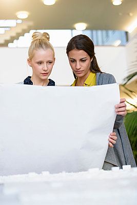 Colleagues discussing town planning drawings in office - p429m1557629 by suedhang photography