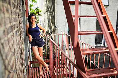 Portrait of smiling woman standing on urban fire escape - p555m1303230 by Granger Wootz