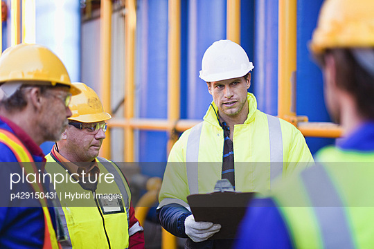 Workers talking on oil rig - p42915043f by Hybrid Images