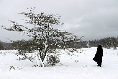Woman standing in the snow - p1019m739809 by Stephen Carroll
