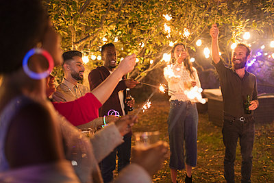 Playful friends with sparklers enjoying garden party - p1023m2161409 by Paul Bradbury