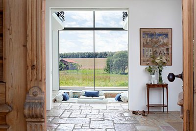View of hallway and living room of modern country house with panoramic windows through open front door - p1183m997114 by Bauer, Christine