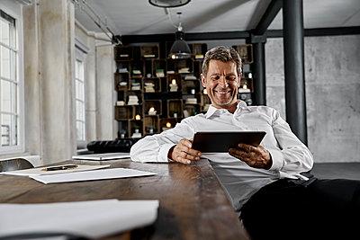 Smiling mature man using digital tablet in loft office - p300m1581277 von Philipp Dimitri