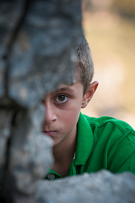 Young boy looking through the rocks  - p794m1119731 by Mohamad Itani