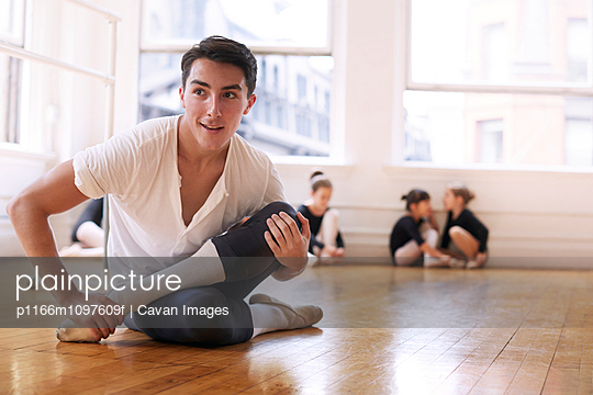 Smiling ballet dancer exercising while sitting on hardwood floor at studio