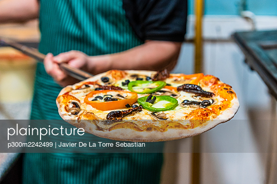 Mid section of chef holding peel with freshly made pizza - p300m2242499 by Javier De La Torre Sebastian