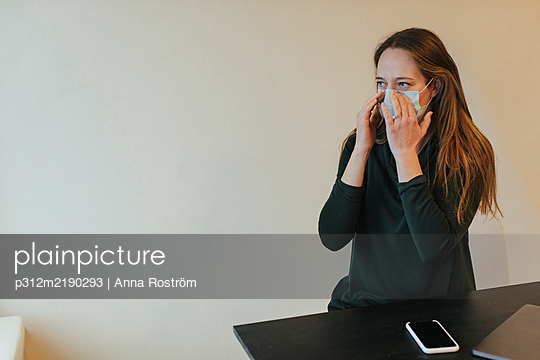 Woman wearing protective mask in office - p312m2190293 by Anna Roström