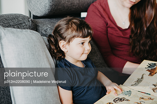 Girl with book sitting on sofa - p312m2208090 by Madeleine Wejlerud