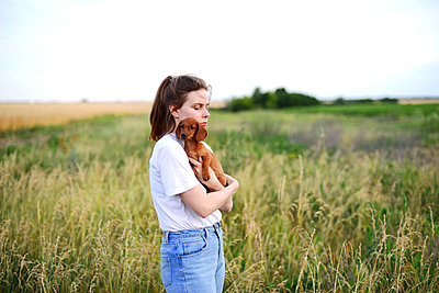 Young woman hugging her small  dog in a park - p1166m2096583 by Cavan Images