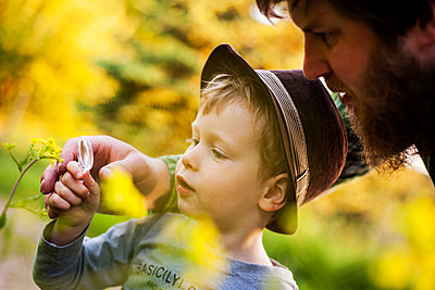 Portrait of little boy exploring nature with magnifying glass - p300m949012 by Andreas Pacek