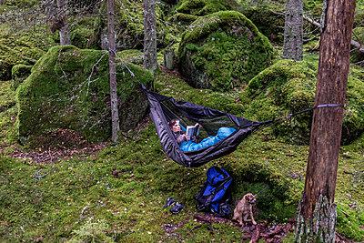 Woman reading book in hammock in forest - p312m2049732 by Fredrik Schlyter