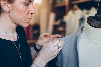Fashion designer pinning garment onto dressmaker's dummy - p429m2058369 by Eugenio Marongiu