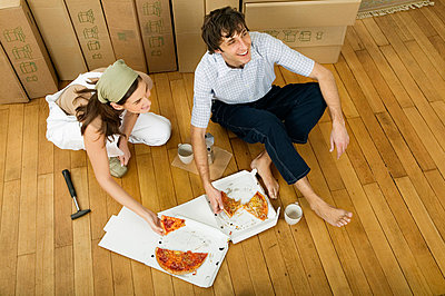 Couple eating pizza in new home - p6090355f by DRESDEN photography