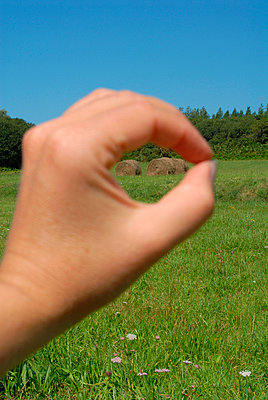 Hand forming a circle to see a bale of hay - p6810028 by Sandrine Léon
