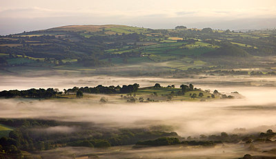 Early morning mist hanging over rolling farmland near Llangadog, Brecon Beacons National Park, Carmartenshire, Wales, United Kingdom, Europe - p8713053 by Adam Burton