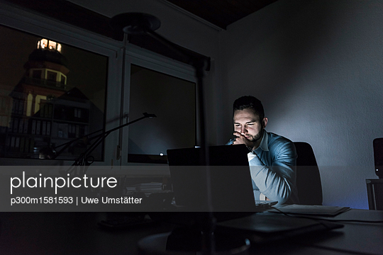Businessman working on laptop in office at night - p300m1581593 von Uwe Umstätter