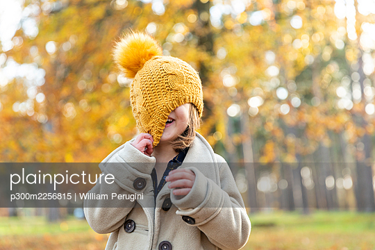 Playful girl covering face with knit hat while standing at forest - p300m2256815 by William Perugini