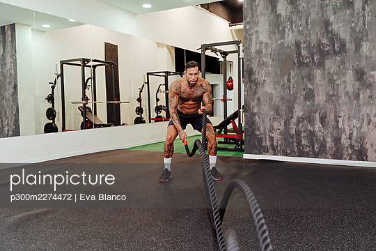 Male athlete exercising with rope in gym - p300m2274472 by Eva Blanco