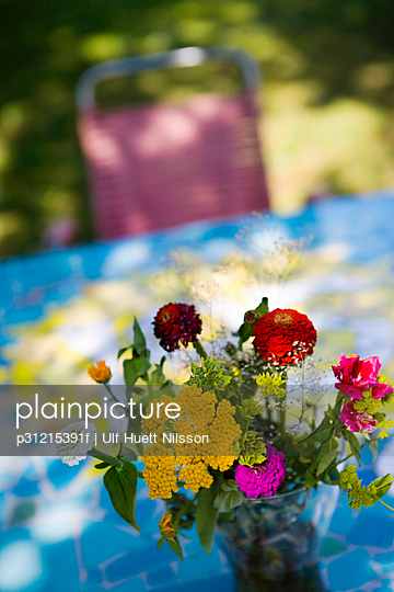 Brightly-coloured flowers on a table outside.