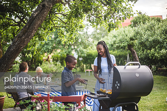 Mother and son preparing food on barbecue grill in yard during weekend party - p426m2135615 by Maskot