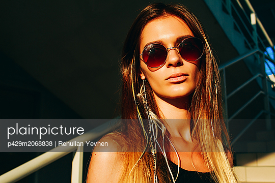 Young woman with long brown hair and sunglasses on stairway, head and shoulder portrait - p429m2068838 by Rehulian Yevhen