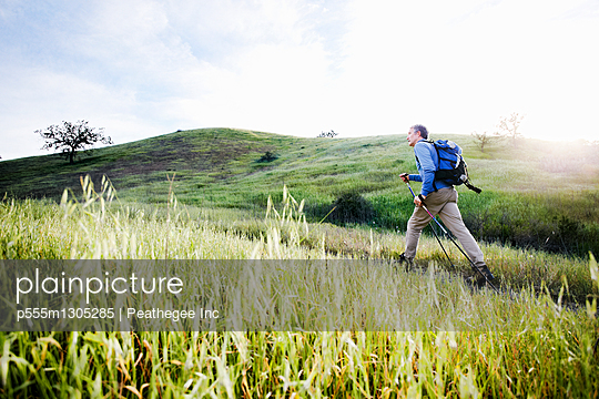 Caucasian man hiking in on mountain path - p555m1305285 by Peathegee Inc