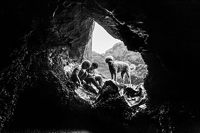 Two children looking down with dog in sea cave - p1166m2095285 by Cavan Images