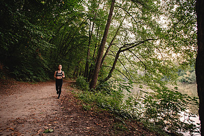 Front view of young woman jogging in forest by lake - p1166m2095773 by Cavan Images