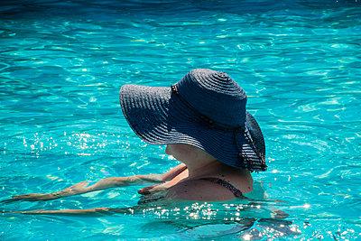 Woman in blue hat in swimming pool - p1418m1571845 by Jan Håkan Dahlström