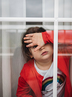 Little girl looking out of window - p1522m2168618 by Almag