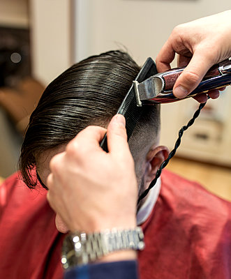 Hairdresser shaving young man's hair in a barbershop - p300m1018805f by Marco Govel