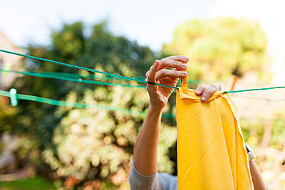 Close-up of woman hanging up yellow blanket on clothesline - p300m1580823 by Valentina Barreto