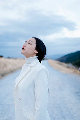 Young woman with eyes closed standing on road - p300m2241694 by Tania Cervián