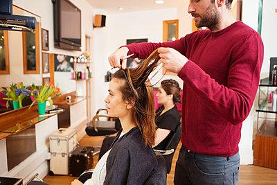 Female customer having long brown hair trimmed in hair salon - p429m1408148 by Nancy Honey