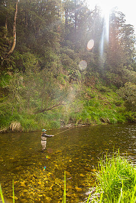 Caucasian woman fishing in remote river - p555m1312268 by Steve Smith