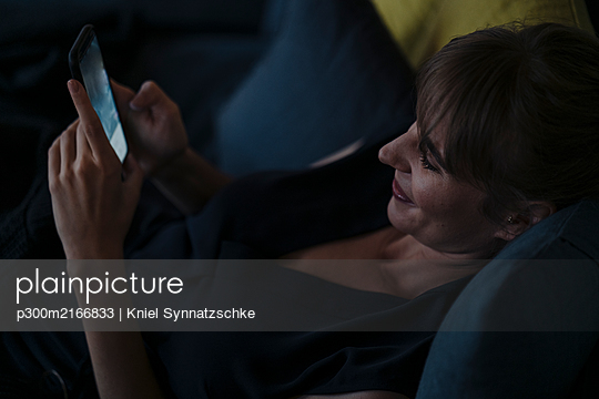 Smiling woman using cell phone on couch - p300m2166833 by Kniel Synnatzschke