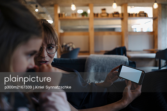 Woman and girl sitting on couch in office using smartphone - p300m2167339 by Kniel Synnatzschke