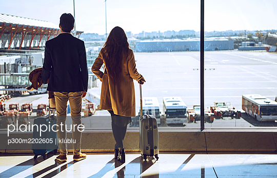 Business couple looking through window at airport departure area - p300m2202605 by klublu