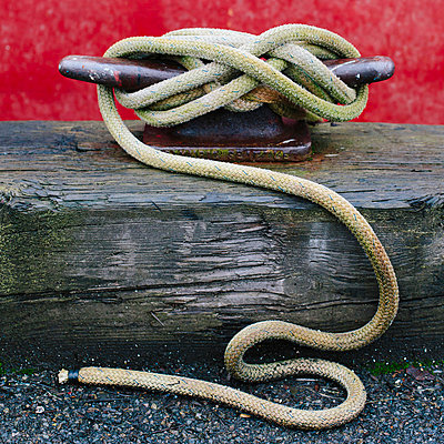 Close up of a wharfside mooring cleat with a fishing boat rope tied around it.  - p1100m876226f by Paul Edmondson