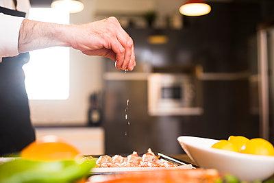 Crop chef salting fresh prawns - p1166m2124196 by Cavan Images