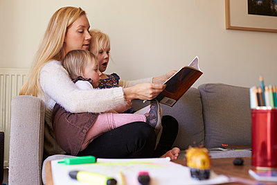 Mother Sitting On Sofa Reading Story With Daughters - p1407m1507748 by Monkey_Images
